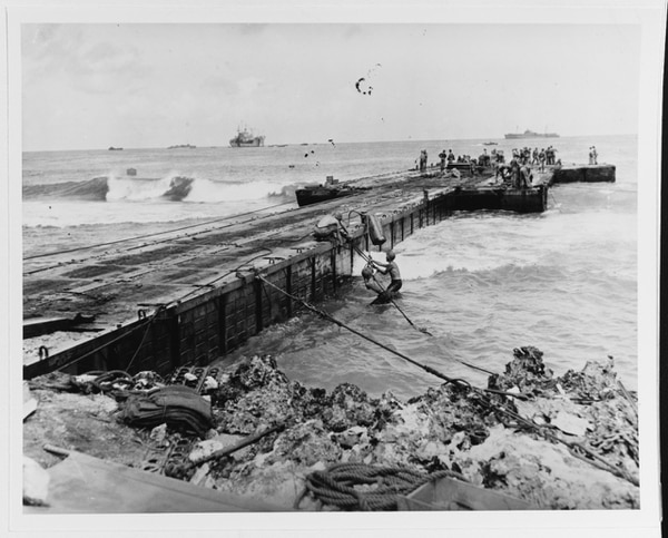 Caption: Men of the 302nd Construction Battalion repair a pontoon causeway that had broached at Tinian's White 2 beach during a storm, 1 August 1944. (U.S. Naval History and Heritage Command)