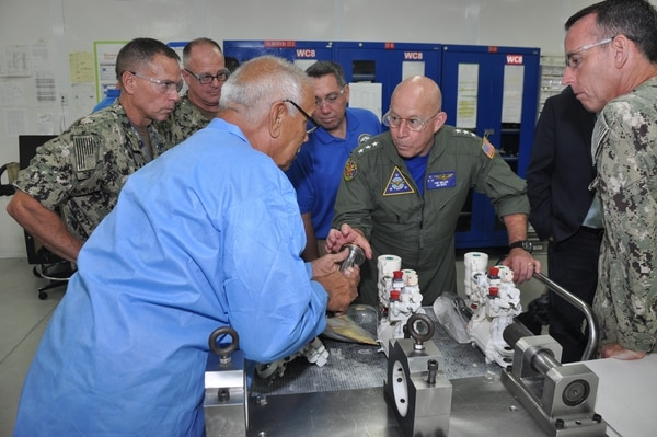 Naval Air Forces commander Vice Adm. DeWolfe Miller receives a brief on F/A-18 Super Hornet actuators Sept. 17 inside Fleet Readiness Center Southwest's Building 472. (Christopher Nette/Navy)