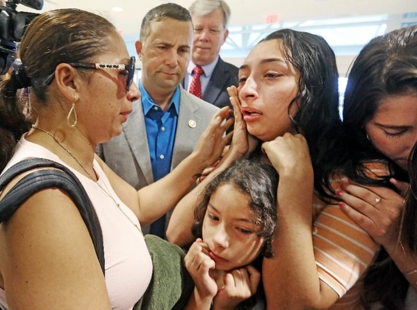 Alejandra Juarez, 38, left, says goodbye to her children, Pamela and Estela, at the Orlando International Airport on Friday, Aug. 3, 2018 in Orlando, Fla. Juarez, the wife of a former Marine sergeant, is preparing to self-deport to Mexico in a move that would split up their family. (Red Huber/Orlando Sentinel via AP)