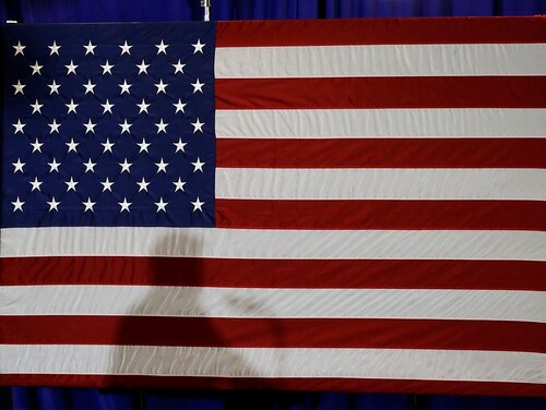 In this Aug. 31, 2018, file photo, President Donald Trump's shadow is shown on an American flag as he speaks before signing an executive order at the CPCC Harris Conference Center in Charlotte, N.C. (Chuck Burton/AP)