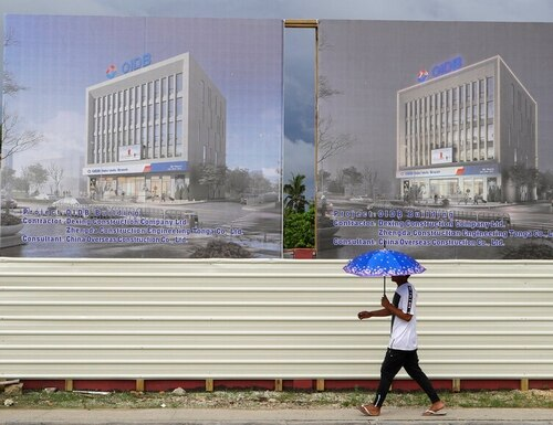 A man walks past a development site for a Chinese investment bank in Nuku'alofa, Tonga, on April 10. (Mark Baker/AP)