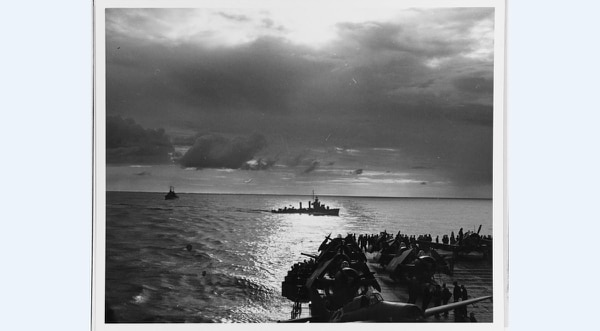 A destroyer passes astern of the aircraft carrier RANGER at sunset on Nov. 8, 1942, the first day of landings on North Africa. Note F4F Wildcat fighters on the Ranger's deck. (National Archives)