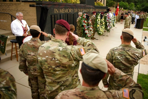 In this Thursday, May 24, 2018, photo, soldiers salute as taps play at the U.S. Army Special Operations Command Fallen Special Operations Soldier Memorial ceremony on Fort Bragg, N.C. The names of four Special Forces soldiers killed last year in an ambush in Niger are among those that have been added to the memorial wall at Fort Bragg. (Andrew Craft /The Fayetteville Observer via AP)