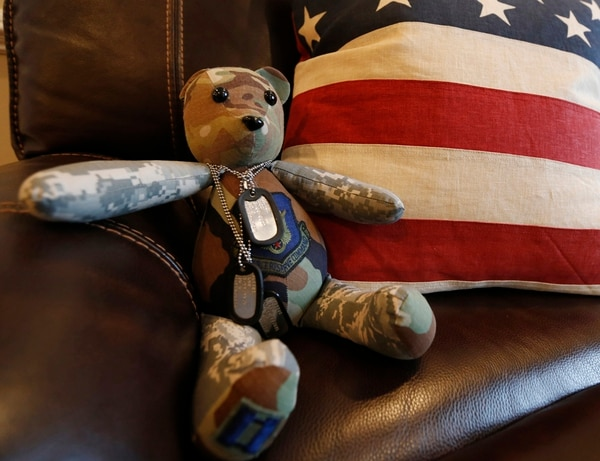 This Dec. 16, 2014, photo shows a stuffed animal wearing the dog tags of the late Army Major Chad Wriglesworth on the chair where he died in Bristow, Va. Wriglesworth died of cancer after returning from deployment in Afghanistan. By the hundreds, other widows, widowers, parents, siblings and children are sharing accounts of their grief as part of the largest study ever of America's military families as they go through bereavement. (AP Photo/Steve Helber)