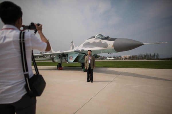 A spectator poses for photos before a MiG-29 aircraft during the second day of the Wonsan Friendship Air Festival in Wonsan, North Korea, on Sept. 25, 2016. (Ed Jones/AFP via Getty Images)