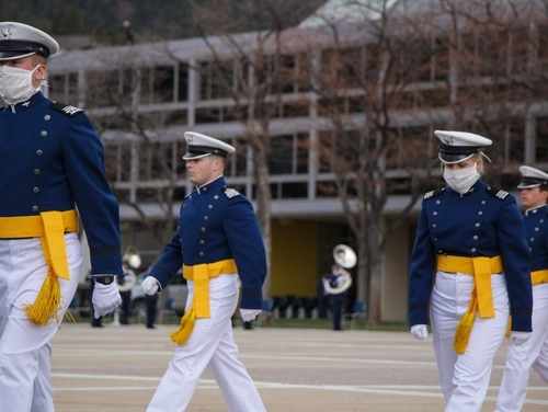 Graduating cadets at the Air Force Academy, some wearing facemasks to protect against the coronavirus, walk to their commencement ceremony April 19. The academy is starting to reopen some services and lift restrictions on who can visit. (Air Force)