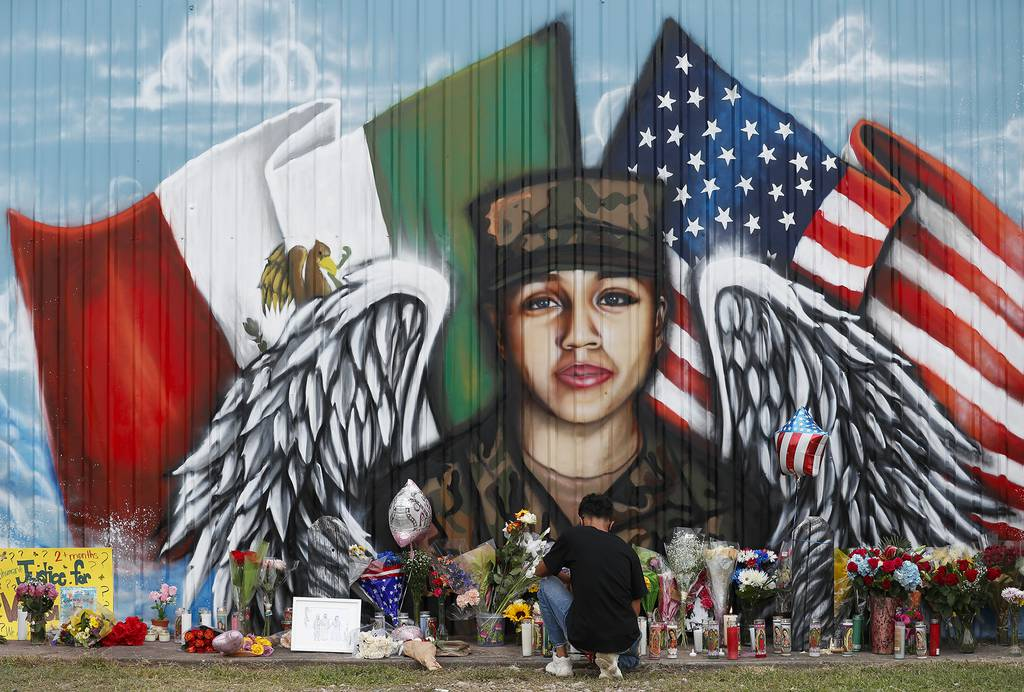 Juan Cruz, boyfriend of Army soldier Vanessa Guillén, kneels in front of a mural honoring her on July 5, 2020, in Houston.