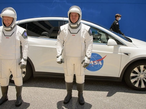 NASA astronauts Douglas Hurley, left, and Robert Behnken, wearing SpaceX spacesuits, are seen as they depart the Neil A. Armstrong Operations and Checkout Building for Launch Complex 39A during a dress rehearsal prior to the Demo-2 mission launch, Saturday, May 23, 2020. (NASA/ Bill Ingalls)