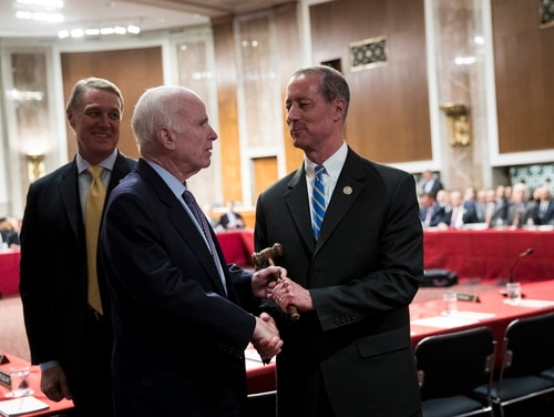 Sen. John McCain, center, R-Ariz., hands over the gavel to Rep. Mac Thornberry, R-Texas, at the start of meeting between the Senate and House Armed Services committees on Oct. 25, 2017, in Washington. (Drew Angerer/Getty Images)