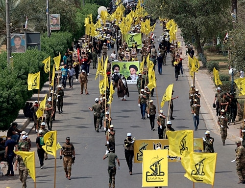 In this June 8, 2018, file photo, Iraqi Popular Mobilization Forces march as they hold their flag and posters of Iraqi and Iranian Shiites spiritual leaders during