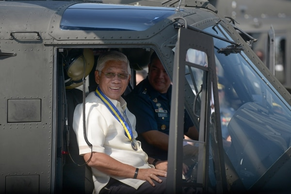Philippine Defence Secretary Voltaire Gazmin poses in the cockpit of a newly delivered Bell 412 helicopter during a christening ceremony in Manila on Aug. 17, 2015. (Jay Directo/AFP)