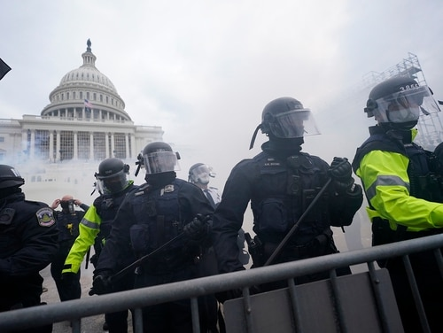 In this Jan. 6, 2021, file photo, police stand guard after holding off violent rioters who tried to break through a police barrier at the Capitol in Washington. (Julio Cortez/AP)