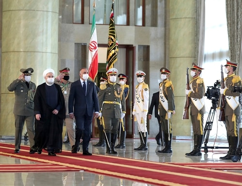 Iraqi Prime Minister Mustafa al-Kadhimi, fourth left, reviews an honor guard as he is welcomed by President Hassan Rouhani, second left, as they all wear protective face masks to help prevent spread of the coronavirus, during an official arrival ceremony, in Tehran, Iran, Tuesday, July 21, 2020. (Iranian Presidency Office via AP)
