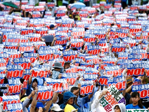 Protesters display signs against a planned Marine base relocation during a rally in Naha, Okinawa prefecture, on the southern Japanese island Saturday. (Koji Harada/Kyodo News via AP)
