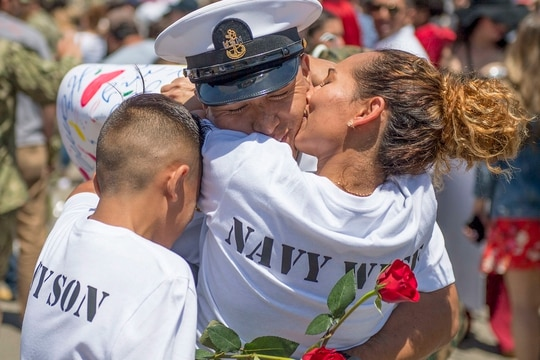 Chief Aviation Boatswain's Mate (Fuel) Miguel Mosquera, assigned to the Nimitz-class aircraft carrier USS Theodore Roosevelt (CVN 71), hugs his family upon the ship's return to San Diego from a scheduled deployment. Theodore Roosevelt departed San Diego, Oct. 6, 2017 and spent the deployment supporting Operations Inherent Resolve and Freedom's Sentinel, as well as maritime security cooperation efforts in U.S. 5th and 7th Fleet areas of operation. (MCSN Nick Bauer/Navy)