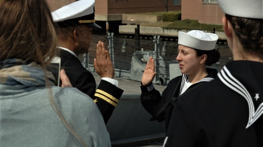 Aviation Machinist Mate 3rd Class Alyssa Anguiano, assigned to the aircraft carrier Dwight D. Eisenhower, reenlisted on board Norfolk's decommissioned battleship on March 15. To meet retention goals, the Navy offered $195 million in re-up bonuses in 2020. (Max Lonzanida/U.S. Navy).