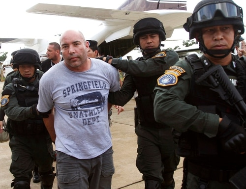 In this Sept. 26, 2013, file photo, Joseph Hunter, second from left, a former U.S. Army sniper who became a private mercenary, is in the custody of Thai police commandos after being arrested in Bangkok, Thailand. (Sakchai Lalit/AP)
