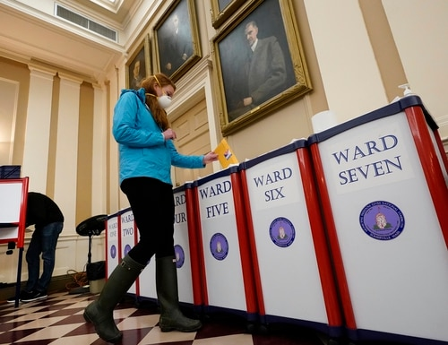 A voter drops her ballot into the box during early in-person voting at City Hall, Thursday, Oct. 29, 2020, in Somerville, Mass. (AP Photo/Elise Amendola)