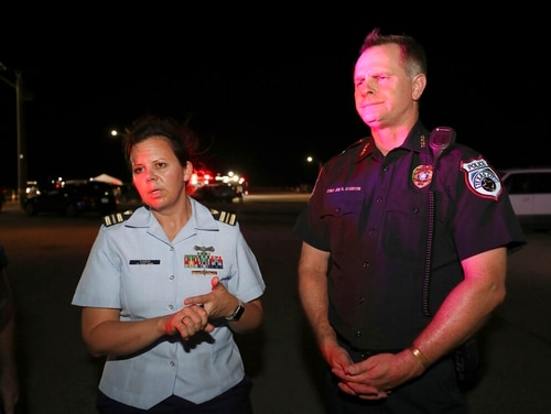 U.S. Coast Guard Lt. Cmdr. Caren Damon, left, and Texas City Police Chief Joe Stanton talk about the search for Kemah Police Chief Chris Reed after he was thrown overboard from his pleasure craft by a wave from a large vessel as he was boating near the Texas City Dike on Friday. (Jennifer Reynolds/The Galveston County Daily News via AP)