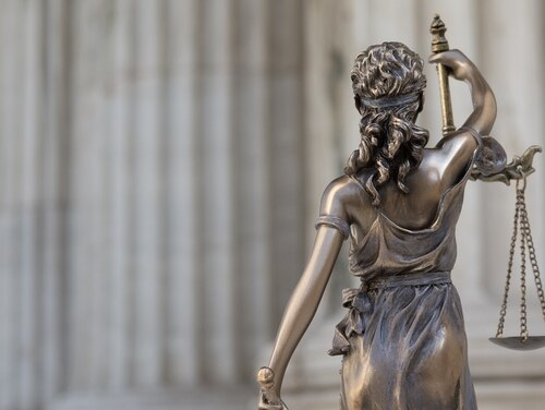 The statue of justice Themis or Justitia, the blindfolded goddess of justice against an ionic order colonnade, as a legal concept