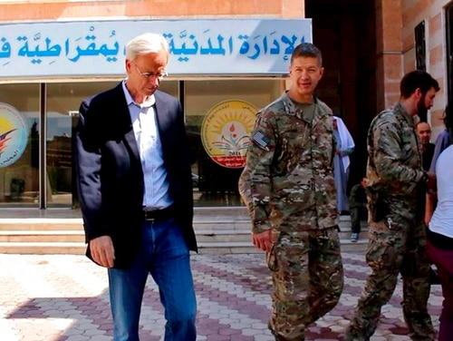This photo released by Hawar News, the news agency for the semi-autonomous Kurdish areas in Syria, shows the head of the anti-ISIS U.S. coalition, Maj. Gen. James Jarrard, center, and veteran Middle East diplomat William Roebuck, left, in the town of Manbij, in Aleppo province, Syria, Thursday, June 7, 2018. (Hawar News via AP)