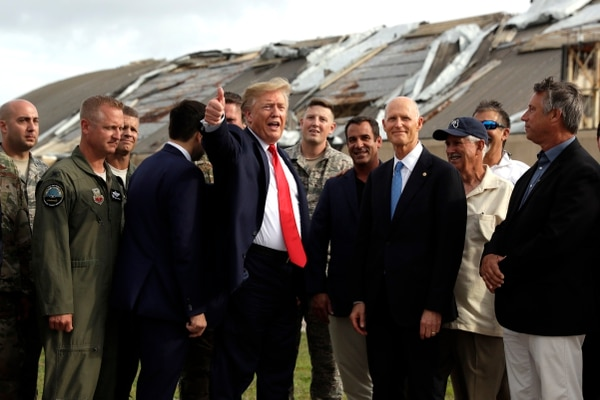 President Donald Trump speaks with base and political officials May 8 as he tours areas of Tyndall Air Force Base, Fla., that were damaged by Hurricane Michael. (Evan Vucci/AP)