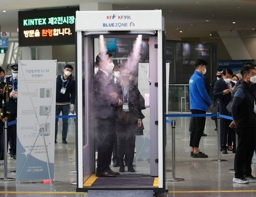 An attendee of DX Korea 2020 stands in a sterilizer as a precaution against the novel coronavirus on Nov. 18, 2020. (Ahn Young-joon/AP)