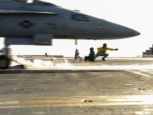 150429-N-KU391-058 U.S. 5TH FLEET AREA OF OPERATION (April 29, 2015) A shooter launches an F/A-18C Hornet assigned to the Thunderbolts of Marine Strike Fighter Attack Squadron (VMFA) 251 on the flight deck of the aircraft carrier USS Theodore Roosevelt (CVN 71). Theodore Roosevelt is deployed to the U.S. 5th Fleet area of operations conducting maritime security operations. (U.S. Navy photo by Mass Communication Specialist 3rd Class Josh Petrosino/Released)