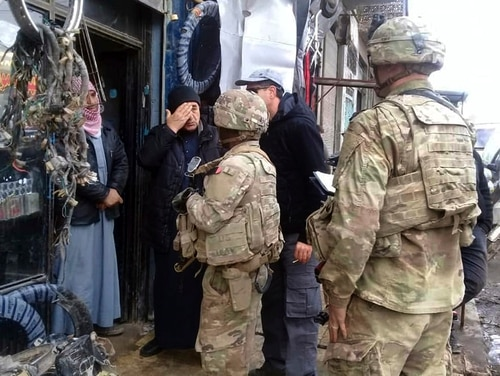 This photo released on the Facebook page of the Military Council of Manbij City in Syria shows U.S. troops based around Manbij speaking with residents in northern Syria, Sunday, Dec. 23, 2018. Syria's military announced Friday, Dec. 28, 2018 that it has entered the Kurdish-held town, where Turkey has threatened an offensive. (The Military Council of Manbij City via AP)