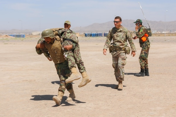 Sgt. Christian Ladd watches as an Afghan medical soldier carries a simulated casualty. (Staff Sgt. Neysa Canfield/Army)