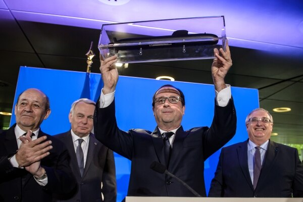 French President Francois Hollande (C) receives a model submarine from French naval defence contractor DCNS chief executive officer Herve Guillou (R) next to French Foreign Minister Jean-Marc Ayrault (2nd-L) and French Defence Minister Jean-Yves Le Drian (L) during a visit to the DCNS headquarters in Paris on April 26, 2016. France beat off competition from Germany and Japan to win a Aus$50 billion (US$39 billion) contract to design and build Australia's next generation of submarines, a decision Tokyo called