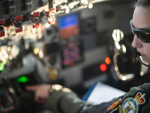 First Lt. Wesleigh Bartels, a pilot with the 351st Air Refueling Squadron, goes over a checklist prior to a flight at RAF Mildenhall, England, Dec. 4. (Tech. Sgt. Emerson Nuñez/Air Force)