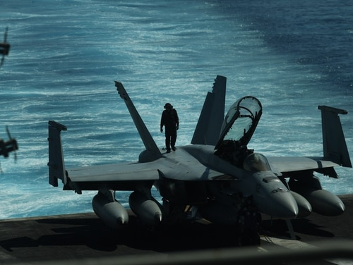 A sailor runs inspections atop an F/A-18 Hornet fighter jet aboard the aircraft carrier Theodore Roosevelt. (Ted Aljibe/AFP via Getty Images)