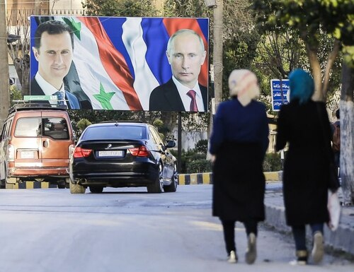 A picture taken on March 9, 2017 in the northern Syrian city of Aleppo, which was recaptured by government forces in December 2016, shows Syrians walking past a giant poster of Syrian President Bashar al-Assad (L) and his Russian counterpart Vladimir Putin (R). / AFP PHOTO / JOSEPH EID (Photo credit should read JOSEPH EID/AFP/Getty Images)