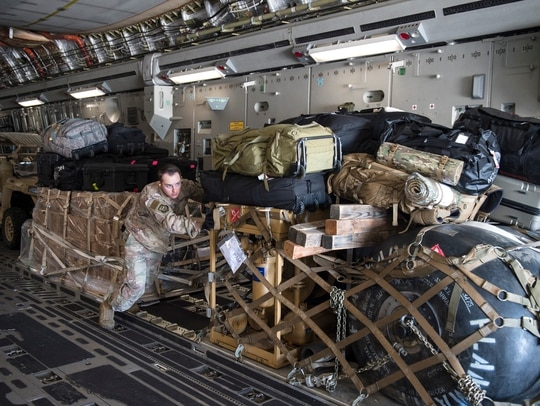 Senior Airman Clinton Andrews, an aerial porter from the 821st Contingency Response Support Squadron, offloads cargo from a Travis Air Force Base C-17 Globemaster III at Tyndall Air Force Base, Florida, Oct. 12. The contingency response team deployed to assess damage and establish conditions for the re-initiation of airflow, bringing much-needed equipment, supplies and personnel for the rebuilding of the base in the aftermath of Hurricane Michael. (Tech. Sgt. Liliana Moreno/Air Force)