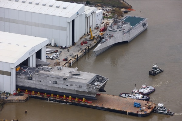 Crews roll out the future expeditionary fast transport Newport before launching it into the Mobile River. That's the future littoral combat ship Mobile above it. (Austal USA)