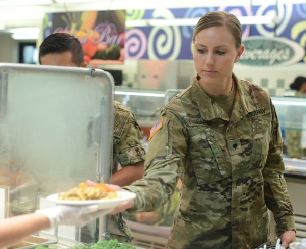 Spc. Mary Calkin, of the Washington National Guard, takes a plate of food at the Freedom Inn Dining Facility at Fort Meade, Md. The Army will transition from the old paper meal card system to an automated meal entitlement code system by Oct. 1. (Joe Lacdan/Army)