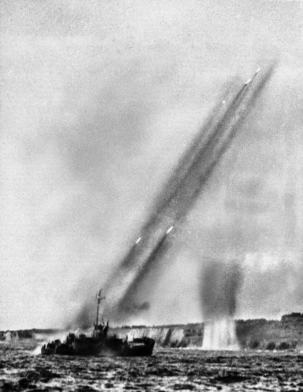 A U.S. landing craft fires rocket projectiles at the rugged shore of Iwo Jima in a pre-invasion bombardment, Feb. 19, 1945. Four rockets trailing smoke can be seen zooming into the air. This photo was made from another landing craft before the Marines stormed ashore. (AP Photo/U.S. Navy/Pool)