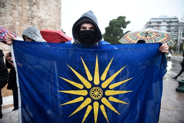 Holding a flag with the Star of Vergina, the emblem of the ancient Greek kingdom of Macedonia and Alexander the Great, an opponent of the Prespa Agreement attends a rally on Jan. 25, 2019. (Giannis Papanikos/AP)