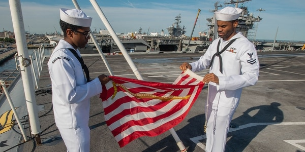 Quartermaster 3rd Class Danaril Mojet, left, and Quartermaster 2nd Class Matthew Lewis, on board the aircraft carrier John C Stennis at Naval Station, Norfolk, fold the warship's First Navy Jack at morning colors on Tuesday. (Mark D. Faram/staff)