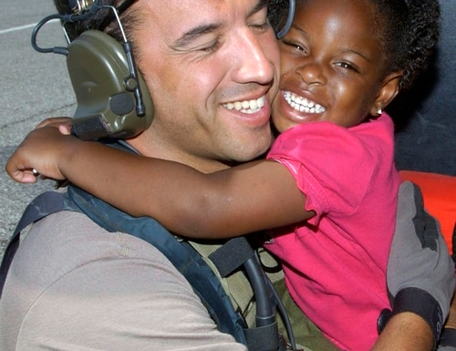 NEW ORLEANS -- A young Hurricane Katrina survivor hugs her rescuer, Staff Sgt. Mike Maroney, after she was relocated to the Louis Armstrong New Orleans International Airport, La., on Sept. 7. Sergeant Maroney is a pararescueman fromm the 58th Rescue Squadron at Nellis Air Force Base, Nev. (U.S. Air Force photo by Airman 1st Class Veronica Pierce)