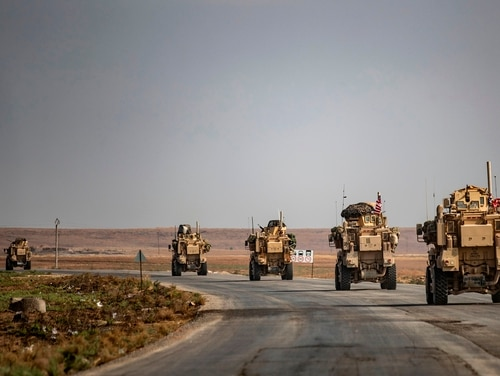 U.S. military vehicles drive on a road in the town of Tal Tamr on Oct. 20, 2019, after pulling out of their base. (Delil Souldeiman/AFP via Getty Images)