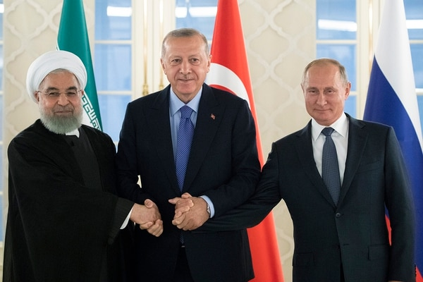 This Sept. 16, 2019, file photo, from left: Iranian President Hassan Rouhani, Turkish President Recep Tayyip Erdogan and Russian President Vladimir Putin shake hands during a meeting in Ankara, Turkey. (Pavel Golovkin, Pool via AP)