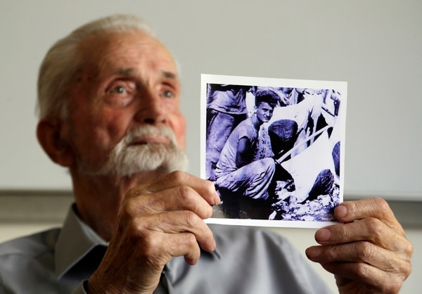 In this Monday, Aug. 7, 2017 photo, WWII veteran Marvin Strombo holds up a photo of himself taken during the battle on Saipan with him holding a captured sword and flag in Portland, Ore. (Don Ryan/AP)