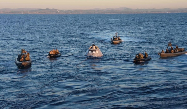 Sailors assist NASA engineers, with the help of Navy divers from Explosive Ordnance Disposal Mobile Unit 3 and sailors from Special Boat Team 12. (MC3 Natalie M. Byers/Navy)
