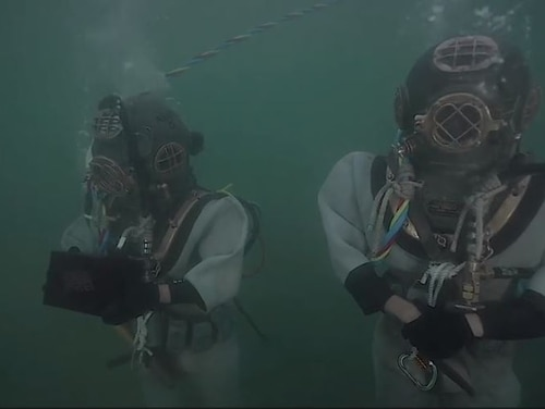 U.S. Army 7th Dive Detachment divers Staff Sgt. Fred Bible and Spc. Julio Melendez interred the remains of Pearl Harbor survivor Lauren Bruner with those of his fellow crewman on board the sunken battleship Arizona during a Dec. 7 ceremony. Bruner will be the last survivor to be interred there. (Screenshot of video recorded by Sgt. Laura Martin/Army)