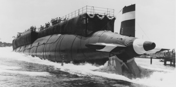 The submarine Thresher enters the water for the first time during launching ceremonies at the Portsmouth Naval Shipyard, Kittery, Maine, on July 9, 1960. It sank less than three years later during deep submergence tests off the coast of New England, killing 112 crew members and 17 civilians. The accident and the probe into it spurred the Navy to to establish stringent safety requirements for submarines to prevent another loss at sea. The submarine safety certification program, called SUBSAFE, ensures that critical systems receive a high quality of documented work. No SUBSAFE-certified submarine has ever been lost. (Naval History and Heritage Command)