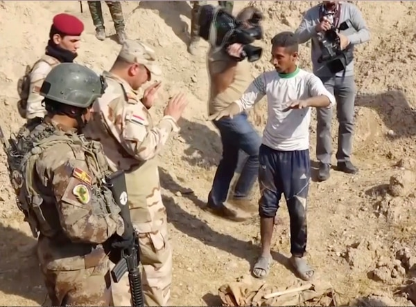 In this Saturday, Nov. 11, 2017, frame grab from video, Iraqi security forces speak to shepherd Khalaf Luhaibi next to bones on the ground, in an area recently retaken from the Islamic State group, at an abandoned base near the northern town of Hawija, Iraq. Kirkuk governor Rakan Saed said Sunday that the bodies of civilians and security forces have been found at the mass grave that could contain up to 400 bodies. (Kirkuk Governor's Office via AP)