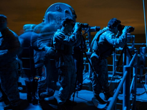 Sailors, and Marines attached to the 22nd Marine Expeditionary Unit stand watch on board the amphibious assault ship Kearsarge as it transits the Strait of Hormuz on Feb. 15. (Mass Communication Specialist 1st Class Mike DiMestico/Navy)