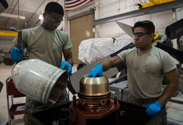 Col. Tom Palenske, commander of the 1st SOW at Hurlburt Field, Fla., is seeking to speed up the process for upgrading airmen's skill levels. Here, Senior Airman Jamal Tabor, left, and Airman 1st Class Michael Brandi replace the seals of a propeller dome at Hurlburt in August 2017. (Airman 1st Class Joseph Pick/Air Force)